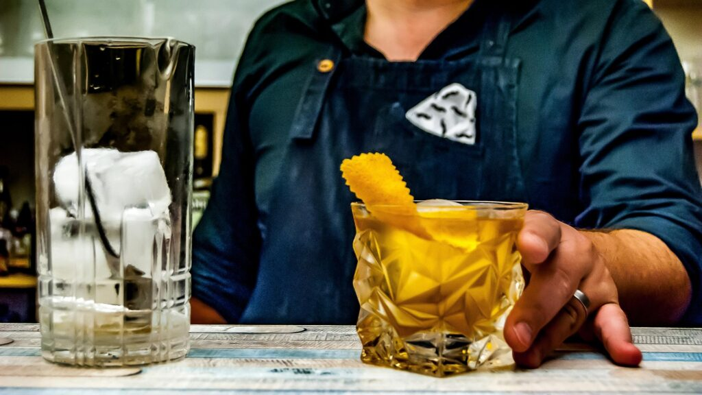 A bartender serving a amber coloured cocktail with a lemon twist