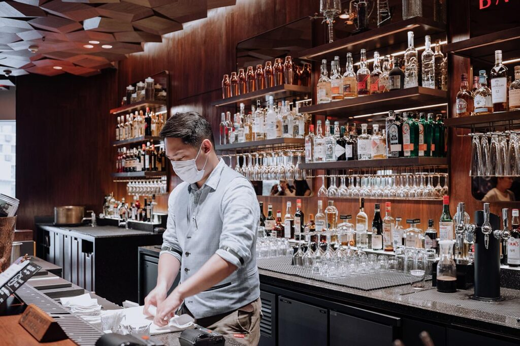 a bartender in mask cleans behind the bar