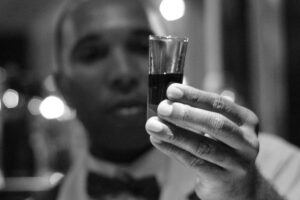 man looking at liqueur in shot glass