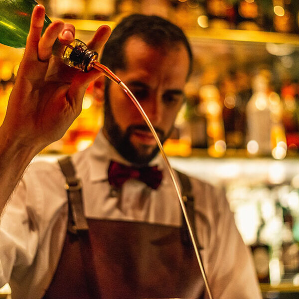 A bartender pours with flair