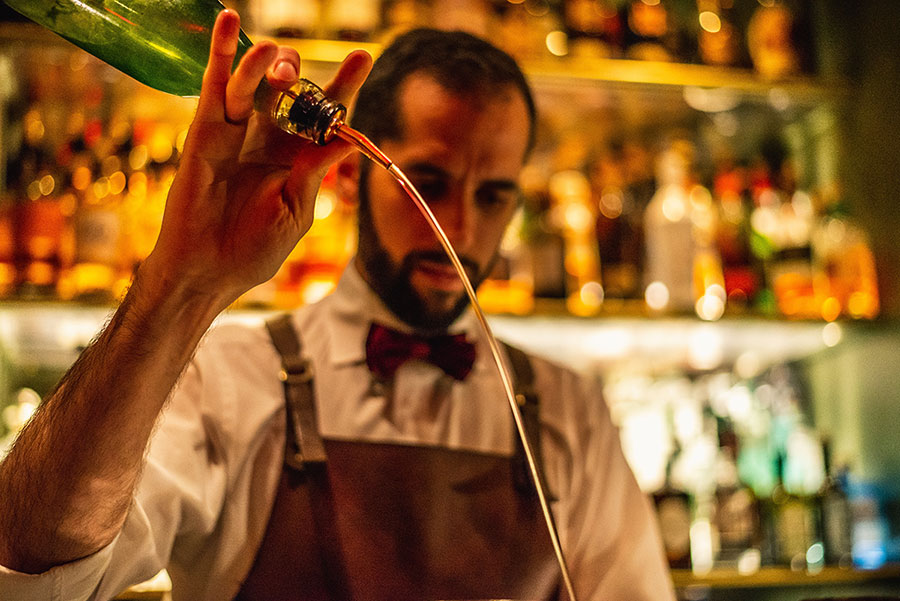 A bartender pours from a speed spout with flair.